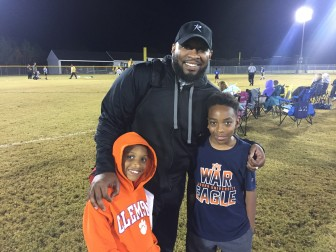 Coach Mike McClure Jr. with his sons Mason, 8 (left), and Xander, 10. Both sons play flag football.