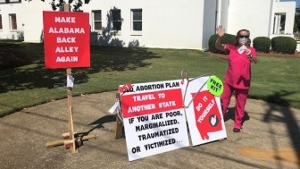 "Laura Stiller of Montgomery protests outside the Alabama State House as the Senate debates an abortion ban. Stiller calls the legislation political and an ""affront to women's rights."""