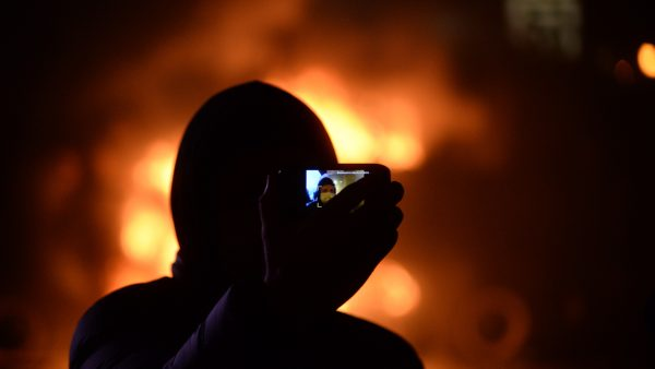 https://wbhm.org/wp-content/uploads/2019/01/Masked_protester_taking_jis_self_portrait_against_background_of_barricades_on_fire._Dynamivska_str._Euromaidan_Protests._Events_of_Jan_19_2014-600x338.jpg