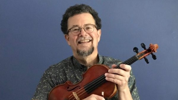 Roger James holding a violin