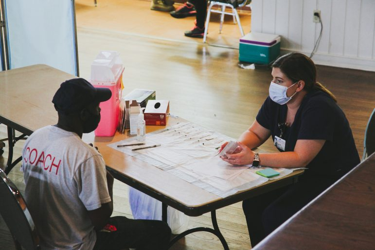 A worker receives a consultation before receiving the vaccine, March 15, 2021.