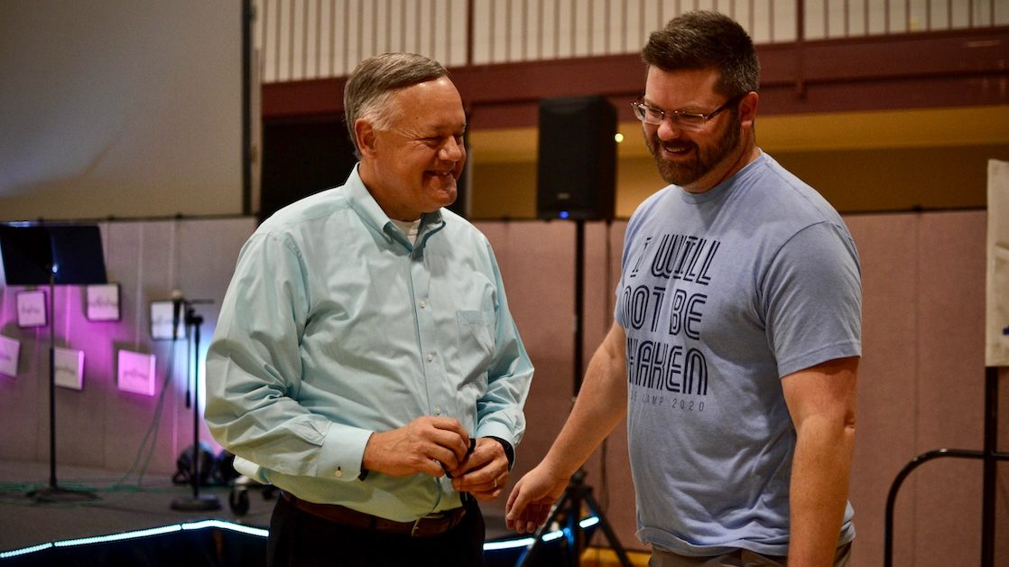Lloyd Sweat, left, pastor at the Meadowood Baptist Church eases youth minister Casey Powell's anxieties about getting his coronavirus vaccine.