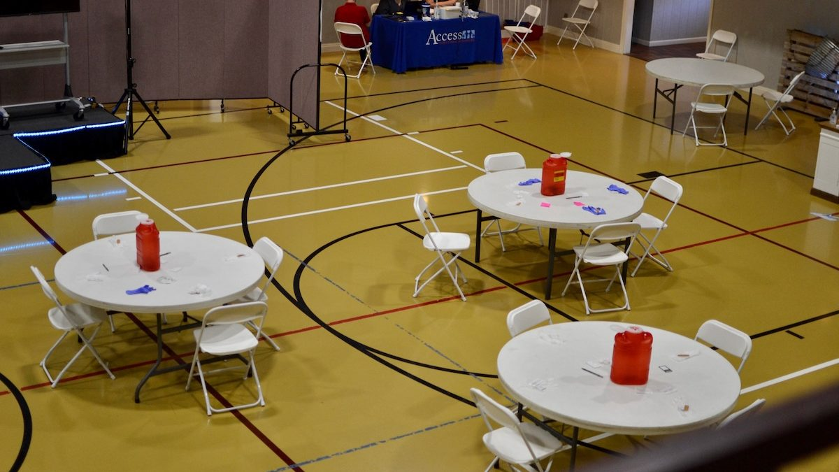 Empty tables and chairs fill the gym of the Meadowood Baptist Church in Amory, Mississippi. The church held a vaccination event with a local community health center, and 30 people trickled through the event to get their vaccines.