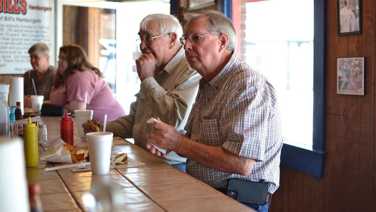 """John Holliman, far right, stopped at Bill's Burgers in downtown Amory, Miss., for lunch said he got his first Moderna shot, but said it """"nearly killed him."""" He's decided not to get his second shot."""