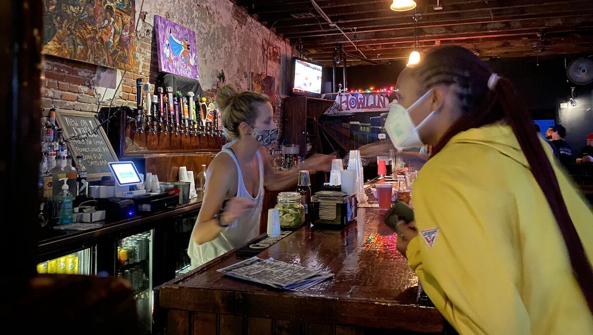 Bartenders and patrons at Howlin' Wolf in New Orleans are required to wear masks in July 2021.