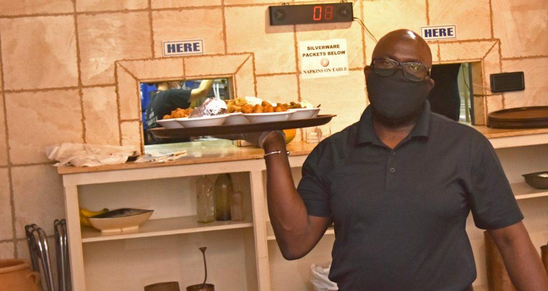 A Fish Market Southside server delivers meals to guests.