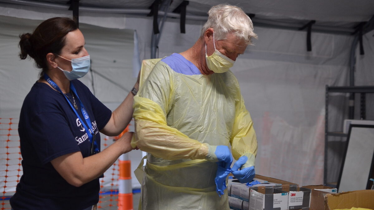 Nurse Kelly Sites helps Nurse John Morris put on his personal protective equipment so that he can treat COVID-19 patients.